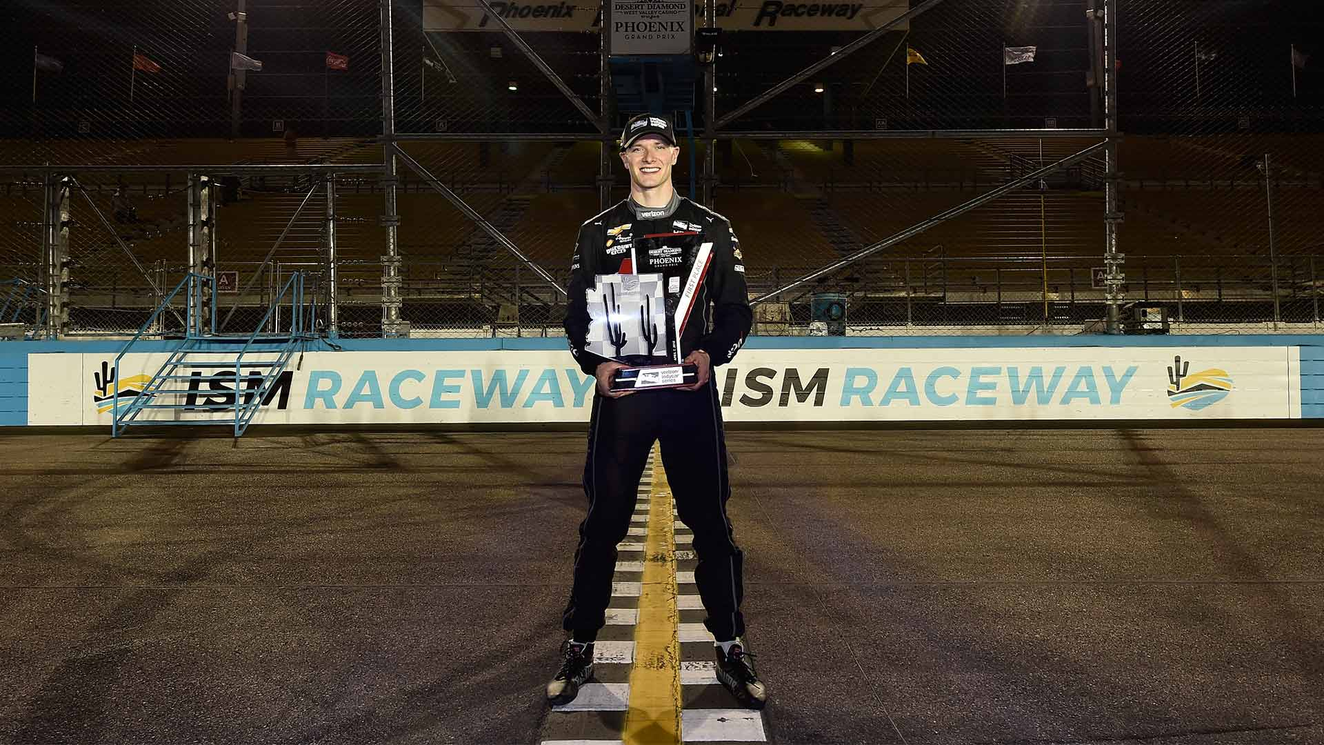 Josef Newgarden stands over the start/finish line with his trophy